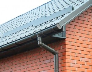 Closeup on new rain gutter system and roof protection from snow board (Snow guard) on house construction
