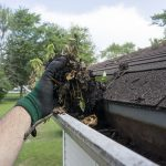 man cleaning out gutters of debris