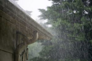Heavy rainstorm pouring down on gutters